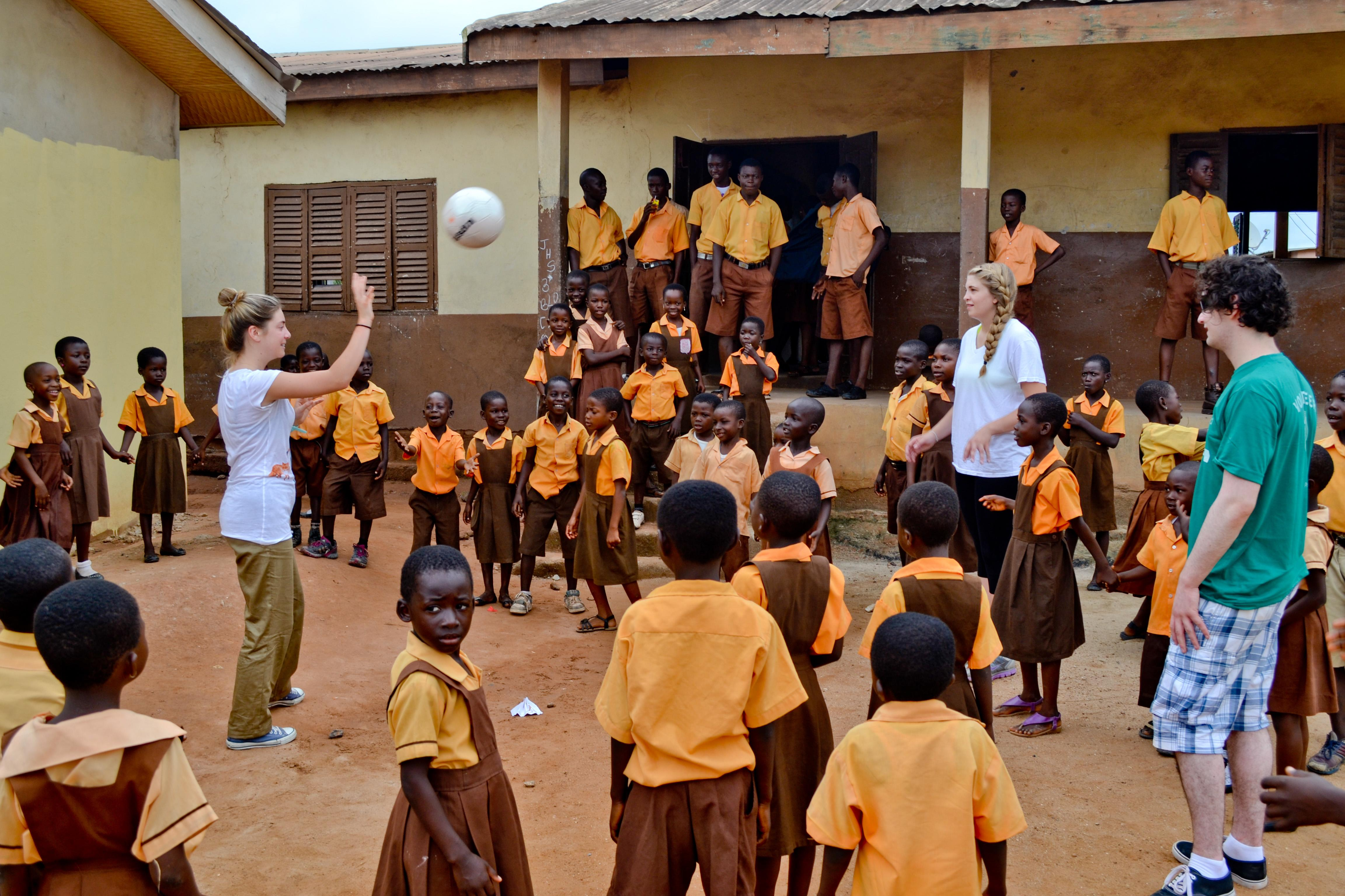 Teaching volunteers in Ghana play football in the school courtyard with their students